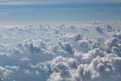 从飞机的窗口您能看到与蓝色和白色云彩的天空 免版税库存图片