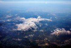从飞机的窗口的看法在阿尔卑斯的积雪覆盖的峰顶的 免版税库存照片