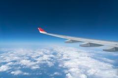从飞机窗口的看法与蓝天和白色云彩 免版税图库摄影