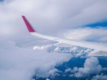 从飞机窗口的看法:在多云天空的翼飞机 库存图片