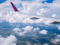 从飞机窗口的看法:在多云天空的翼飞机 库存照片