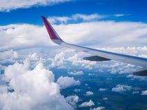 从飞机窗口的看法:在多云天空的翼飞机 免版税库存图片