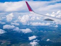 从飞机窗口的看法:在多云天空的翼飞机 免版税库存照片