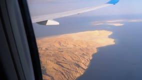 从飞机窗口的鸟瞰图在埃及沙漠、山和红海用清楚的水 股票录像