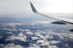 从飞行高在天空的白色云彩上的乘客超音速飞机窗口的美好的顶视图 库存图片