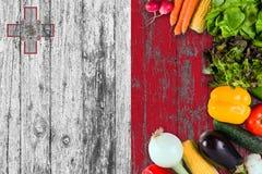 从马耳他的新鲜蔬菜在桌上 烹调在木旗子背景的概念 免版税库存照片