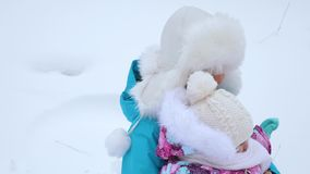 从高多雪的山的妈妈和女儿卷在雪茶碟在冬天和笑 有小孩子的愉快的母亲 股票录像