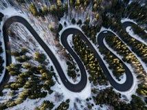 从高山通行证的弯曲道路,在冬时 由寄生虫的鸟瞰图 免版税库存照片