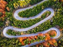 从高山通行证的弯曲道路,在秋天季节,与橙色森林 免版税图库摄影