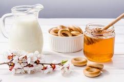 从鲜花甜蜂蜜、新鲜的牛奶和百吉卷的有用的快餐 免版税库存照片