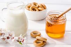 从鲜花甜蜂蜜、新鲜的牛奶和百吉卷的有用的快餐 库存照片