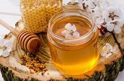 从鲜花甜蜂蜜的自然蜂蜜产品在一个玻璃瓶子,蜂窝,蜂花粉 免版税库存图片