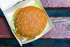 从鸡和莴苣的汉堡包在长凳的红色木板的纸包装 免版税库存图片