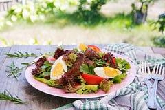 从鸡肝、蕃茄、黄瓜和鸡蛋的温暖的沙拉 免版税库存照片