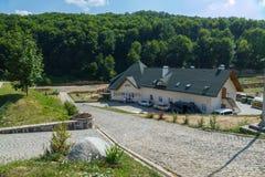 从鹅卵石的通路导致一个大房子,淹没在绿色树的旅馆反对蓝天 库存图片