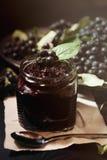 从黑堂梨属灌木Aronia melanocarpa和它的莓果阻塞在黑暗的桌上 自创蜜饯 免版税库存图片