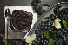 从黑堂梨属灌木Aronia melanocarpa和它的莓果阻塞在黑暗的桌上 自创蜜饯 库存照片