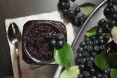 从黑堂梨属灌木Aronia melanocarpa和它的莓果阻塞在黑暗的桌上 自创蜜饯 免版税图库摄影