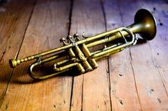 从20世纪30年代的一个精采爵士乐喇叭,在从20世纪20年代的一张木桌上 免版税图库摄影