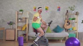 从20世纪80年代的年轻滑稽的运动员与髭订婚锻炼脚踏车显示他的赞许 股票录像