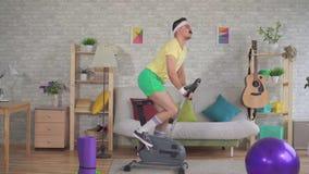 从20世纪80年代的滑稽的运动员与髭参与在公寓的一辆锻炼脚踏车 股票录像