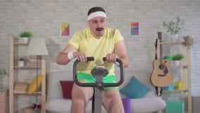 从20世纪80年代的画象滑稽的精力充沛的人运动员与锻炼脚踏车在家允诺的髭缓慢的mo 股票视频