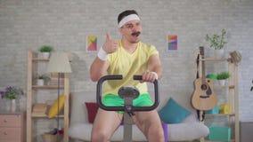 从20世纪80年代的画象精力充沛的人运动员与一辆固定式自行车在家允诺的髭 股票视频