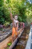 从Asmat部落的年轻十几岁的男孩与在独木舟的桨 库存照片