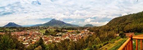 从Kopeng地区的村庄lanscape在显示3座山Merbabu、Telomoyo和安东的三宝垄 免版税库存图片