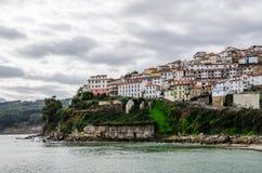 从Lastres海滩的看法Cantabrian海岸的一个村庄在阿斯图里亚斯西班牙 陡峭的表面的白色房子 库存照片