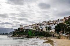 从Lastres海滩的看法Cantabrian海岸的一个村庄在阿斯图里亚斯西班牙 陡峭的表面的白色房子 库存图片