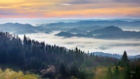 从Luban峰顶的有薄雾的日出风景在Gorce山 库存图片