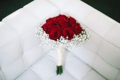 从res玫瑰的婚礼花束在白色沙发 免版税库存照片
