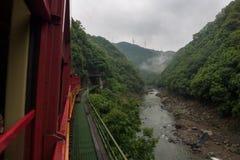 从Sagano盘旋火车的红色无盖货车看见的Katsura河的美好的风景 免版税库存照片