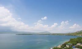 从Sevanavank修道院的看法对市的Sevan 塞凡湖、山、蓝天与云彩和天际 的臂章 库存图片