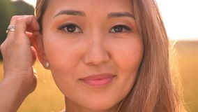 仔细地看和微笑在自然视图的快活的亚裔妇女画象  股票录像