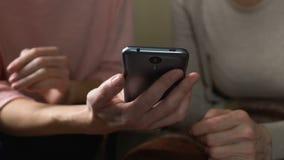仔细的使用现代电话的孙女教的祖母,通信 影视素材