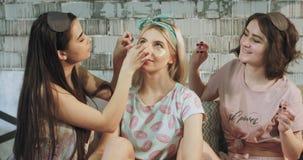 他们在一个白肤金发的夫人上把眼罩放的少年女孩早晨做秀丽惯例,在睡衣 股票视频