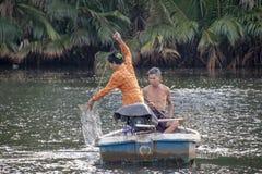他们在河戈公岛忽略了的父亲和女儿使用一个汽船检查鱼网 免版税图库摄影