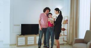 他们有与不动产房地产经纪商的一次交谈观看通过的片剂的年轻夫妇要对买房子 影视素材