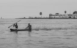 他们独木舟用浆划的男孩 库存照片