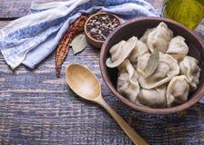 他们的面团和肉末,橄榄油,香料,盐,胡椒,在一个木板的月桂叶自创煮沸的饺子  库存图片