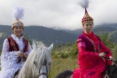 他们的马的地方妇女在全国民俗的展示在阿尔玛蒂,哈萨克斯坦 免版税库存照片