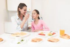 他们获得乐趣在早餐的妈妈和女儿在厨房里坐并且食用早餐 免版税库存图片