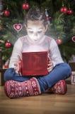他出席在圣诞树下的小女孩开头 库存照片
