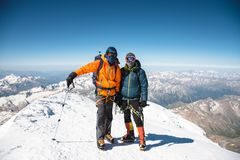 他在他的在途中的朋友旁边站立在上面积雪覆盖的下来夹克和鞔具的画象登山人 库存照片