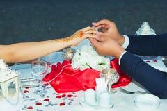 他在她的手指上把她的婚戒放 新郎在可爱的他的手指上把圆环放 微笑的少妇看钻戒 免版税库存图片