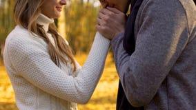 他心爱的妇女的诗人亲吻的手,在秋天木头的浪漫大气 免版税库存照片