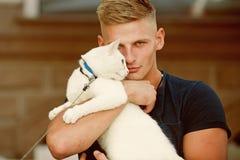 他比宠物是更多 与肌肉神色的愉快的猫所有者 猫在他的所有者的胳膊放松 步行的愉快的人与 库存图片