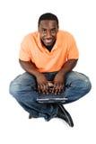 他的使用年轻人的膝上型计算机坐的&# 免版税库存图片